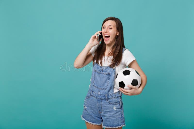 Συγκινημένος εύθυμος οπαδός ποδοσφαίρου νέων κοριτσιών με τη σφαίρα ποδοσφαίρου που μιλά στο κινητό τηλέφωνο που διευθύνει την ευ στοκ φωτογραφίες με δικαίωμα ελεύθερης χρήσης
