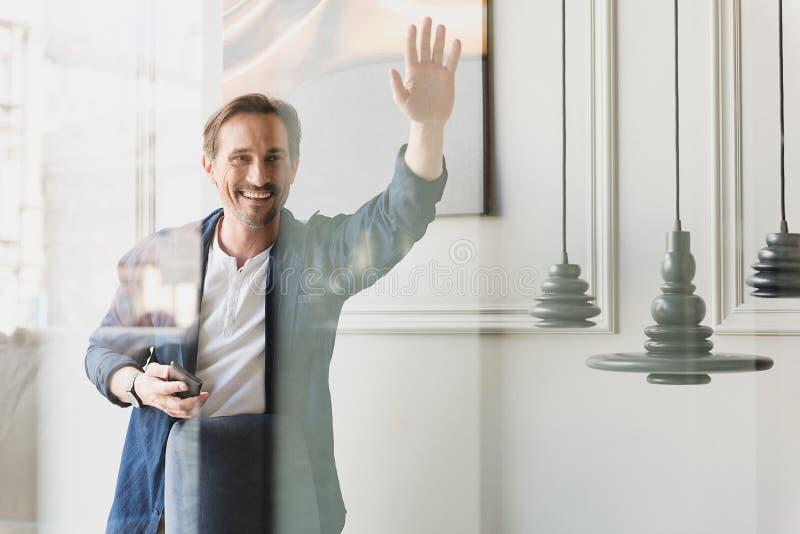 Συγκινημένος φίλος χαιρετισμού επιχειρηματιών μέσω του παραθύρου στοκ φωτογραφία