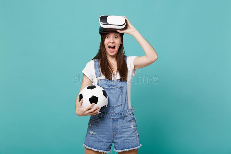 Συγκινημένος χαρούμενος νέος οπαδός ποδοσφαίρου γυναικών στη σφαίρα ποδοσφαίρου εκμετάλλευσης κασκών, παιχνίδι που απομονώνεται σ στοκ φωτογραφία με δικαίωμα ελεύθερης χρήσης
