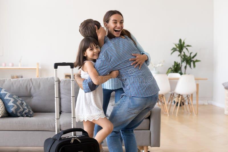 Συγκινημένος mom και ευπρόσδεκτο σπίτι πατέρων αγκαλιάσματος κορών στοκ εικόνα