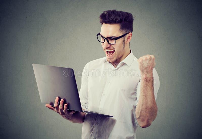 Συγκινημένο άτομο με επιτυχία εορτασμού φορητών προσωπικών υπολογιστών στοκ εικόνα με δικαίωμα ελεύθερης χρήσης