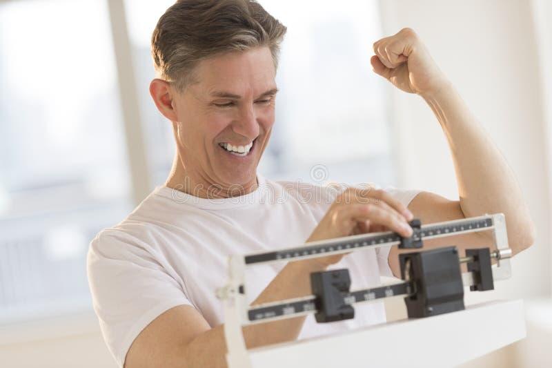 Συγκινημένο άτομο που σφίγγει την πυγμή χρησιμοποιώντας την κλίμακα βάρους στοκ φωτογραφία