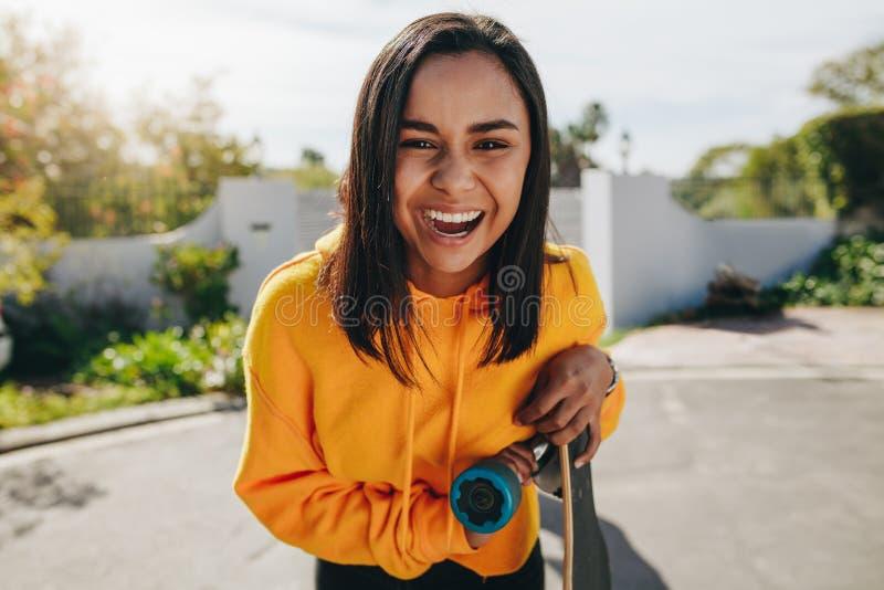 Συγκινημένο έφηβη που στέκεται στην οδό με το longboard της στοκ φωτογραφία