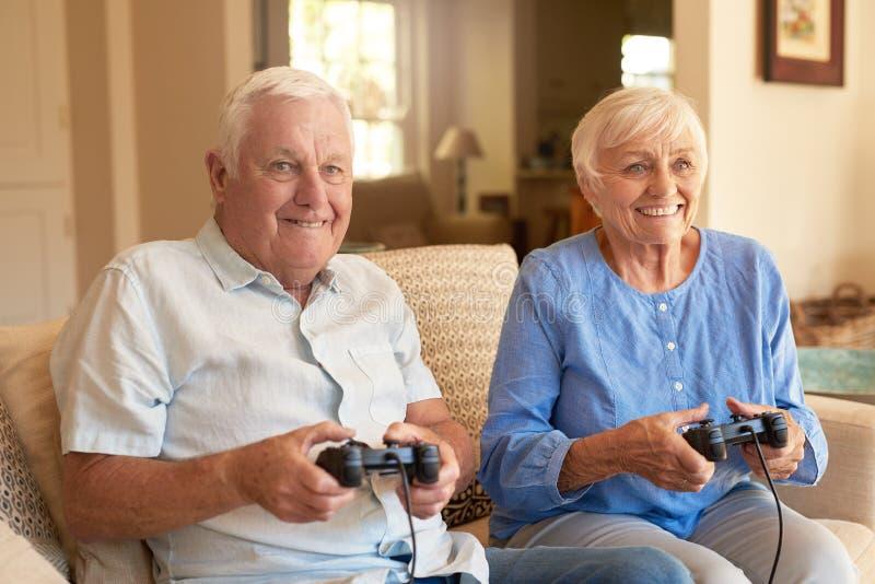 Συγκινημένο ανώτερο ζεύγος που παίζει τα τηλεοπτικά παιχνίδια μαζί στο σπίτι στοκ εικόνα με δικαίωμα ελεύθερης χρήσης