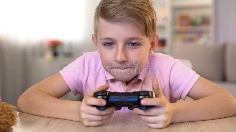 Συγκινημένο αρσενικό παιδί που παίζει το τηλεοπτικό παιχνίδι με την κονσόλα, κίνδυνος προβλημάτων όρασης στοκ φωτογραφία