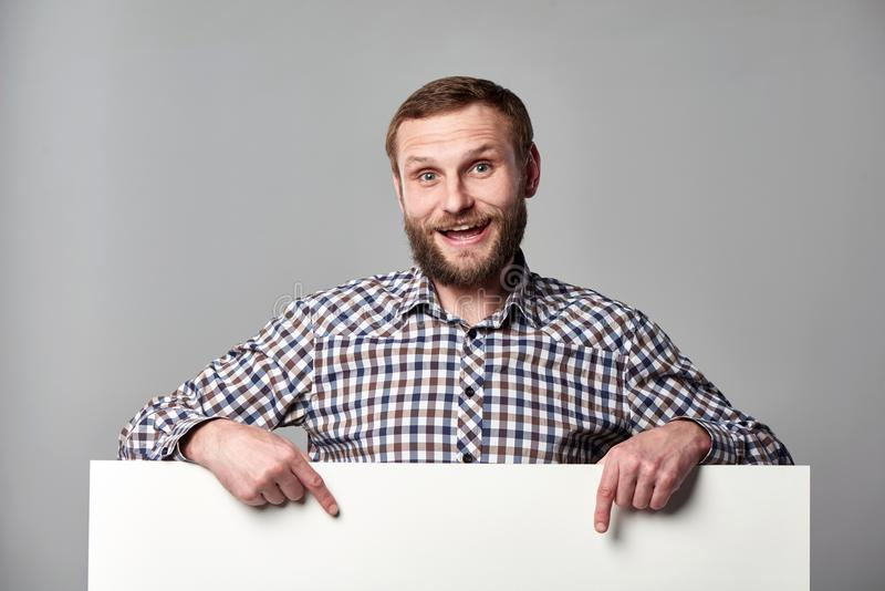 Συγκινημένο γενειοφόρο άτομο με το whiteboard που δείχνει στο κενό διάστημα αντιγράφων στοκ φωτογραφίες
