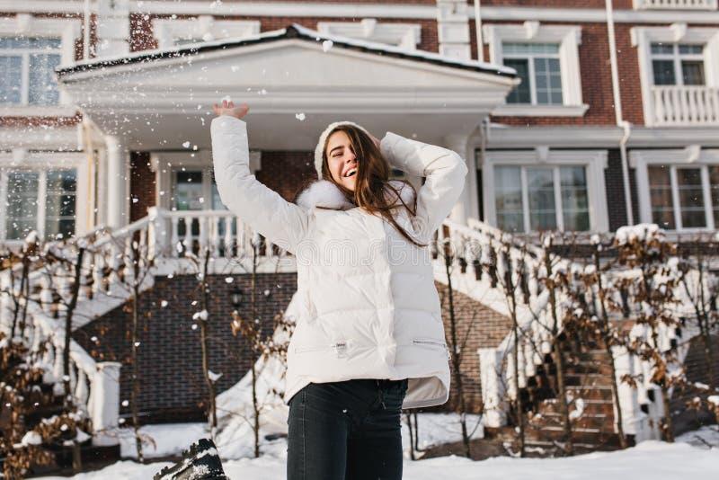 Συγκινημένο θηλυκό πρότυπο που χορεύει και που ρίχνει έξω το χιόνι στην καλή χειμερινή ημέρα Υπαίθριο πορτρέτο του πανευτυχούς μα στοκ φωτογραφία με δικαίωμα ελεύθερης χρήσης