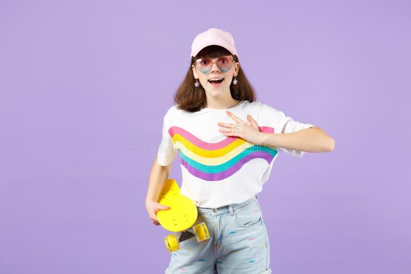 Συγκινημένο κορίτσι εφήβων ζωηρά eyeglasses ενδυμάτων με κίτρινο skateboard που κρατά χέρι στοματικής το ανοικτό εκμετάλλευσης στ στοκ εικόνες με δικαίωμα ελεύθερης χρήσης
