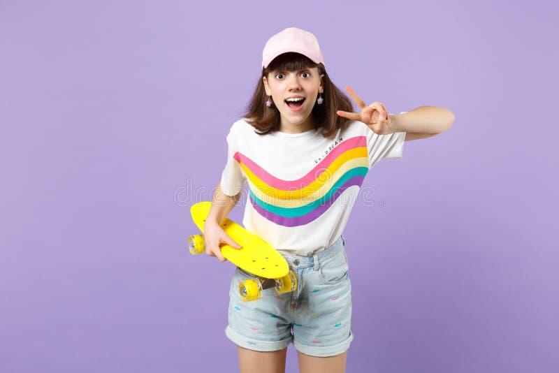 Συγκινημένο κορίτσι εφήβων στα ζωηρά ενδύματα με κίτρινο skateboard, που παρουσιάζει σημάδι νίκης που κρατά το στόμα ανοικτό που  στοκ εικόνες