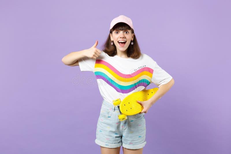 Συγκινημένο κορίτσι εφήβων στα ζωηρά ενδύματα με κίτρινο skateboard, που παρουσιάζει αντίχειρα, που κρατά το στόμα ανοικτό που απ στοκ φωτογραφία με δικαίωμα ελεύθερης χρήσης