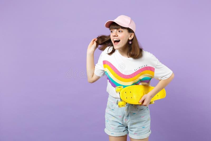 Συγκινημένο κορίτσι εφήβων στα ζωηρά ενδύματα με skateboard την τρίχα εκμετάλλευσης, που κοιτάζει κατά μέρος, που κρατά το στόμα  στοκ φωτογραφίες με δικαίωμα ελεύθερης χρήσης
