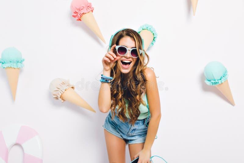 Συγκινημένο κορίτσι με τη λαμπρή σγουρή τοποθέτηση τρίχας στο διακοσμημένο υπόβαθρο που φορά τα σορτς τζιν και τα σκοτεινά γυαλιά στοκ φωτογραφία με δικαίωμα ελεύθερης χρήσης