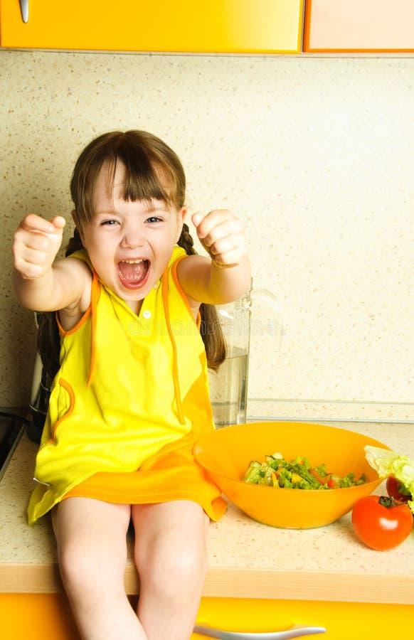 συγκινημένο κορίτσι που κατασκευάζει τη σαλάτα στοκ φωτογραφία