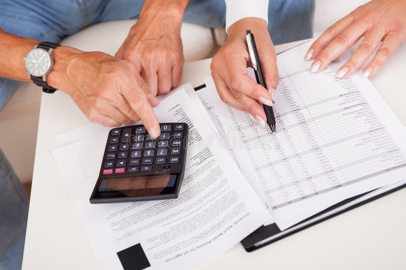 Συγκινημένο μέσης ηλικίας ζεύγος που κάνει τους πόρους χρηματοδότησης στο σπίτι στοκ εικόνα