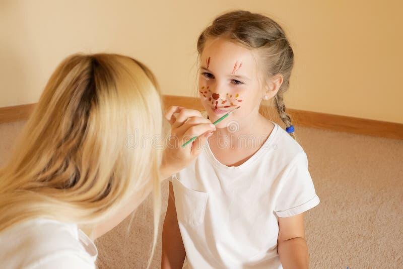 Συγκινημένο μικρό κορίτσι με χρωματισμένο snout που έχει τη διασκέδαση με τη μητέρα που επισύρει την προσοχή στο πρόσωπό της με τ στοκ φωτογραφία