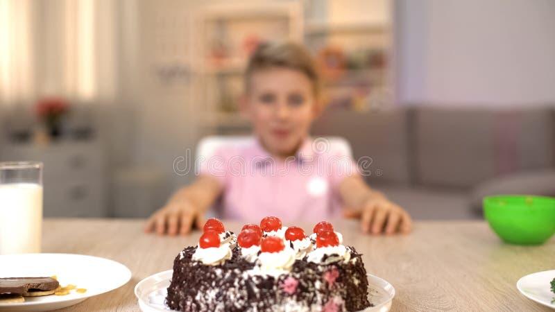Συγκινημένο μικρό παιδί που εξετάζει το εύγευστο κέικ στον πίνακα κουζινών, επιδόρπιο ζάχαρης στοκ φωτογραφία με δικαίωμα ελεύθερης χρήσης