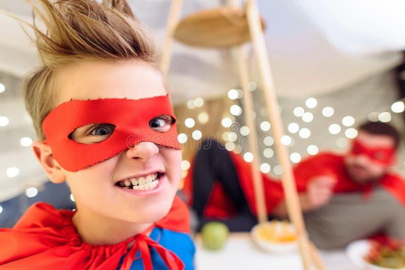 Συγκινημένο μικρό παιδί στο κοστούμι superhero που εξετάζει τη κάμερα στοκ φωτογραφία
