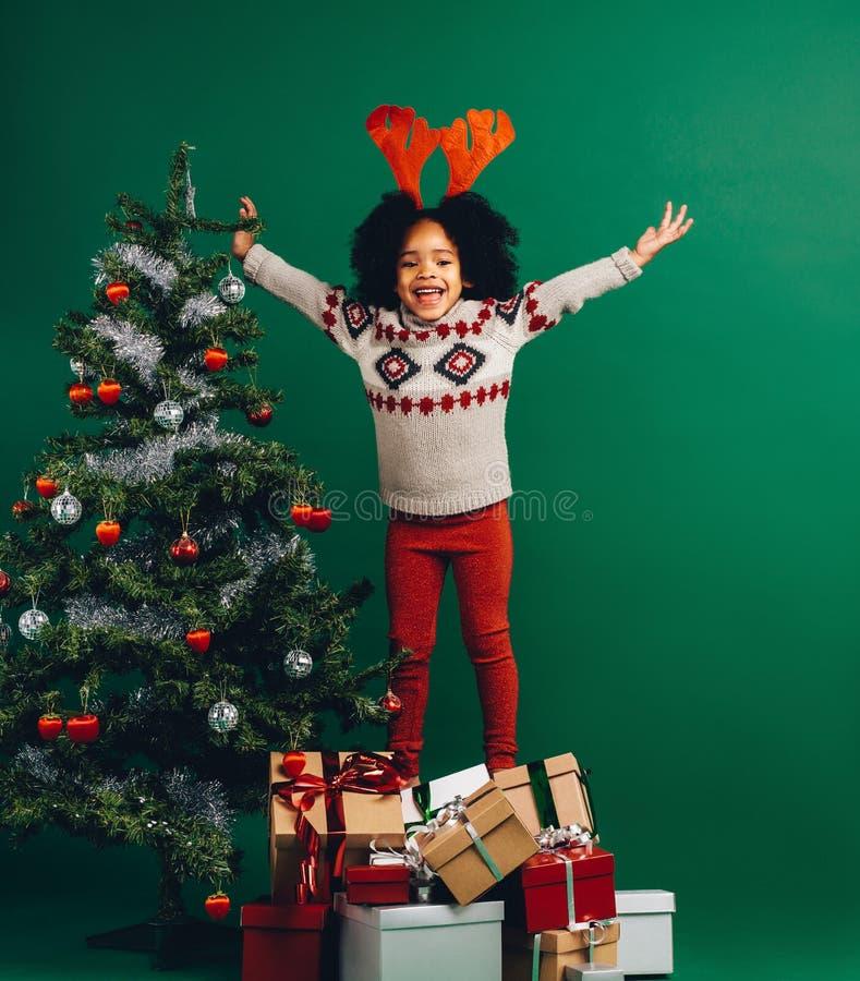 Συγκινημένο παιδί που στέκεται στα κιβώτια δώρων στοκ εικόνες