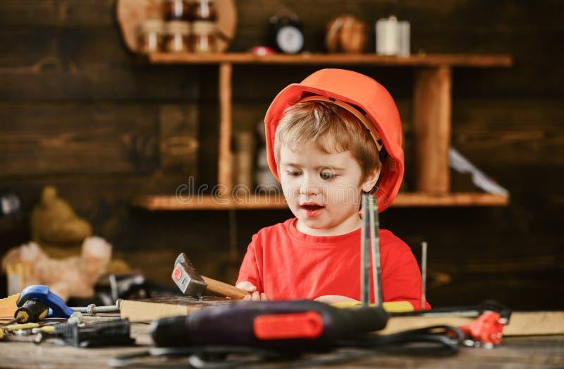 Συγκινημένο παιχνίδι αγοριών με το σφυρί Παιδί που βοηθά στο εργαστήριο Μικρές δεξιότητες ξυλουργών άσκησης παιδιών στοκ φωτογραφία