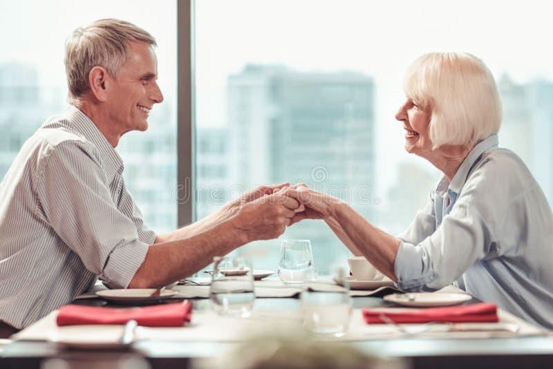 Συγκινημένο συνταξιούχο αίσθημα ζευγών ευτυχές μαζί σε έναν καφέ στοκ φωτογραφία με δικαίωμα ελεύθερης χρήσης