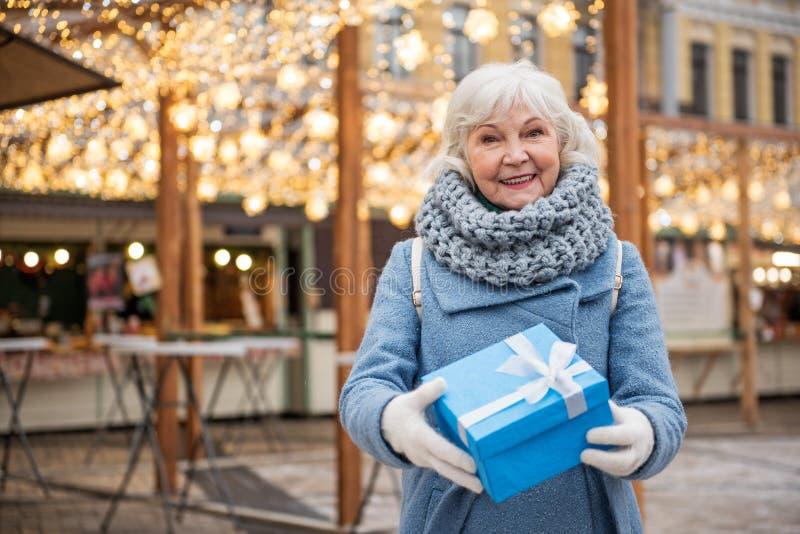 Συγκινημένο ώριμο κιβώτιο δώρων γυναικείας εκμετάλλευσης στοκ φωτογραφία