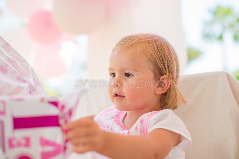 Συγκινημένο Cutie Unwrapping το παρόν γενεθλίων της στοκ εικόνες