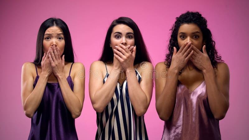 Συγκλονισμένα κορίτσια που κλείνουν το στόμα με τα χέρια στο ρόδινο κλίμα, ειδήσεις κουτσομπολιών στοκ εικόνες με δικαίωμα ελεύθερης χρήσης