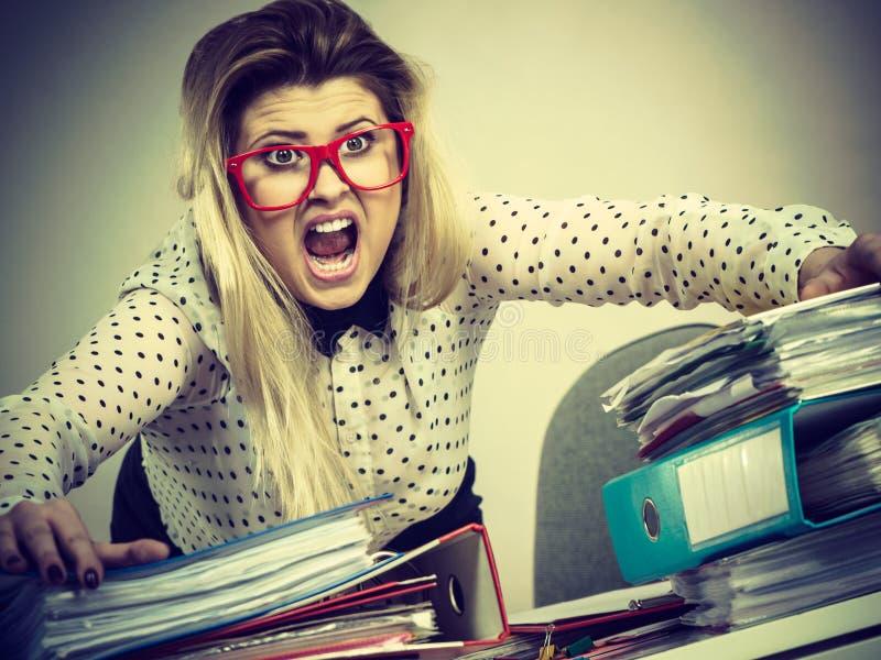 Συγκλονισμένη επιχειρησιακή γυναίκα που εξετάζει τα έγγραφα στοκ εικόνα