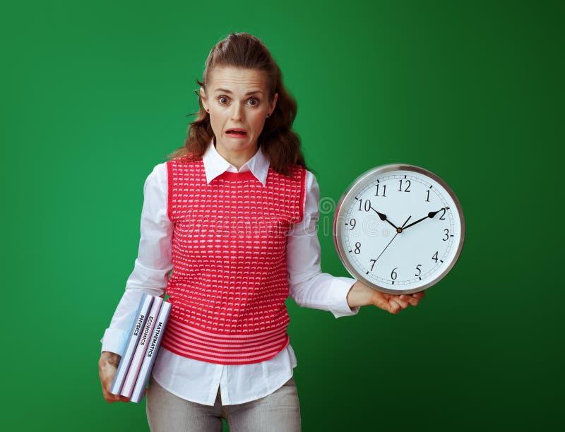 Συγκλονισμένη κατάλληλη γυναίκα αρχαρίων με τα εγχειρίδια και το άσπρο στρογγυλό ρολόι στοκ εικόνες