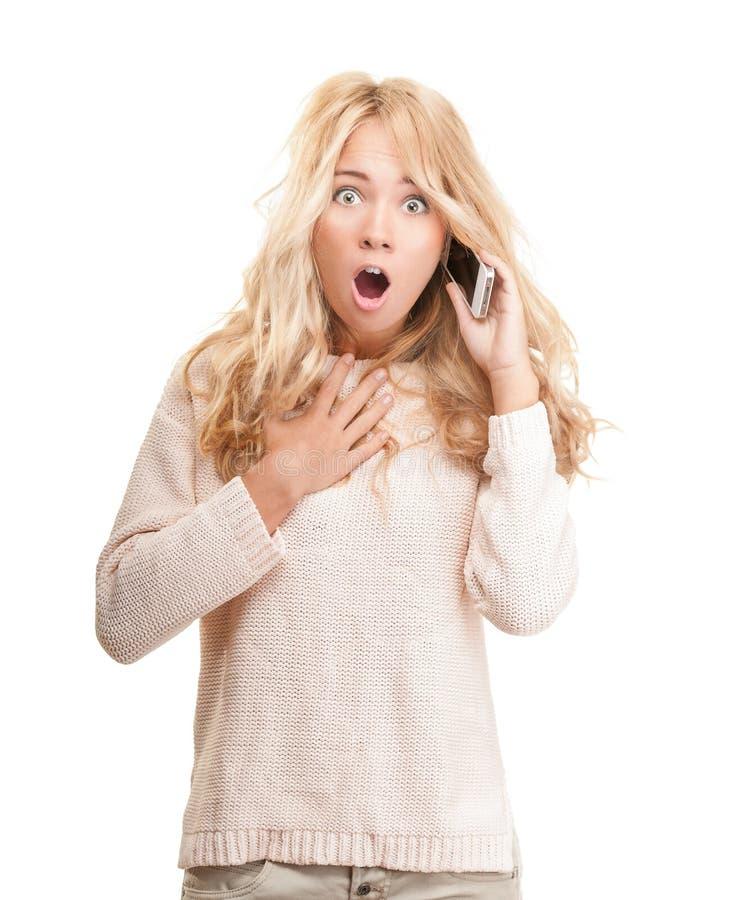 Συγκλονισμένη νέα γυναίκα που μιλά στο τηλέφωνο στο λευκό. στοκ εικόνες