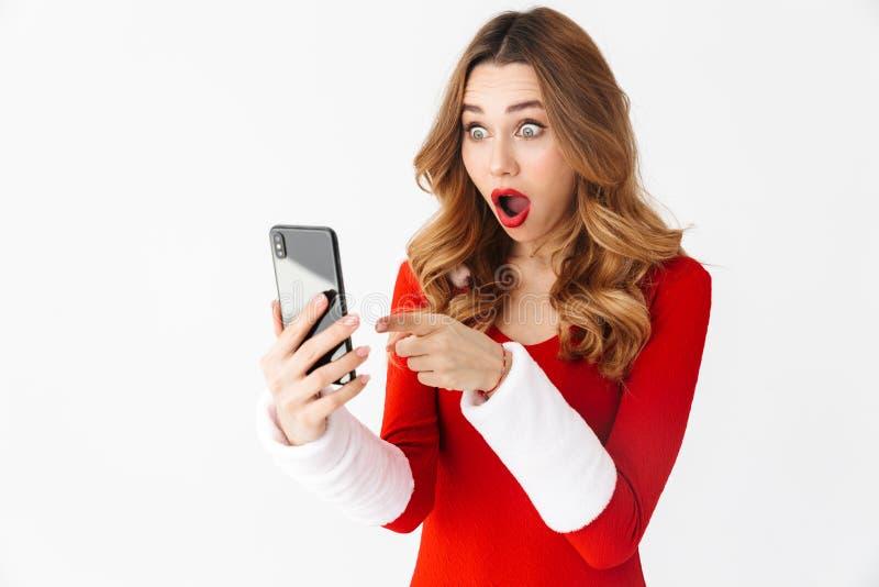 Συγκλονισμένη συγκινημένη γυναίκα στο κοστούμι Χριστουγέννων που χρησιμοποιεί το κινητό τηλέφωνο στοκ εικόνα