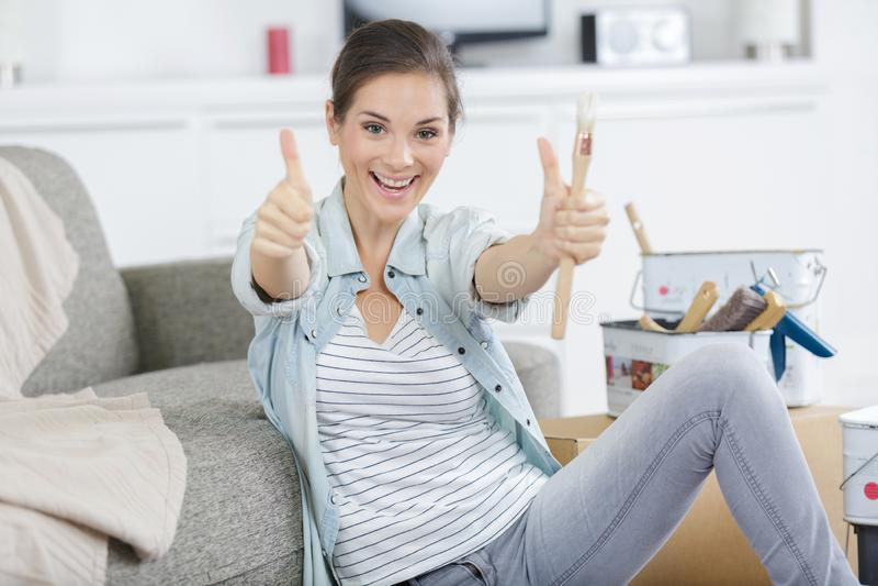 Συγκλονισμένη όμορφη νέα γυναίκα που χαμογελά για την επιτυχία diy στοκ φωτογραφία