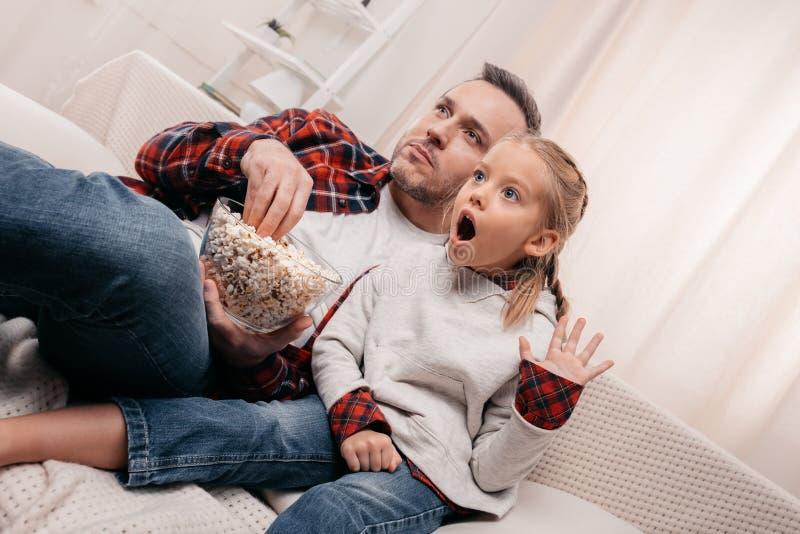 συγκλονισμένοι πατέρας και κόρη που τρώνε popcorn και που προσέχουν τη TV από κοινού στοκ εικόνα με δικαίωμα ελεύθερης χρήσης