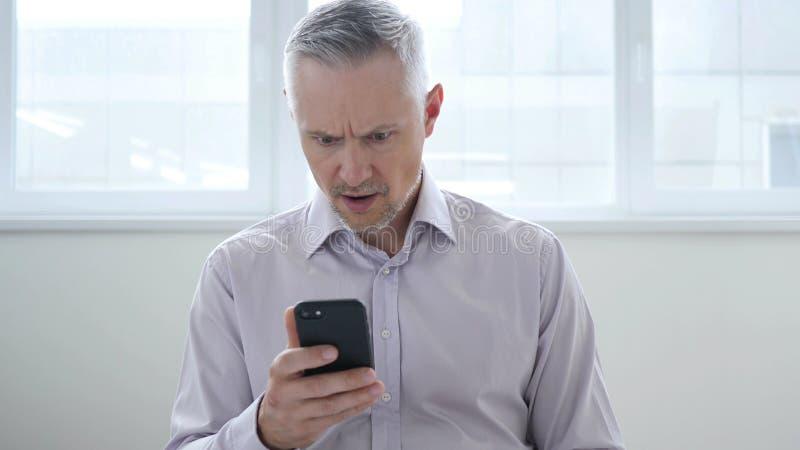 Συγκλονισμένος, έκπληκτος μέσος ηλικίας επιχειρηματίας που χρησιμοποιεί Smartphone στοκ φωτογραφίες με δικαίωμα ελεύθερης χρήσης