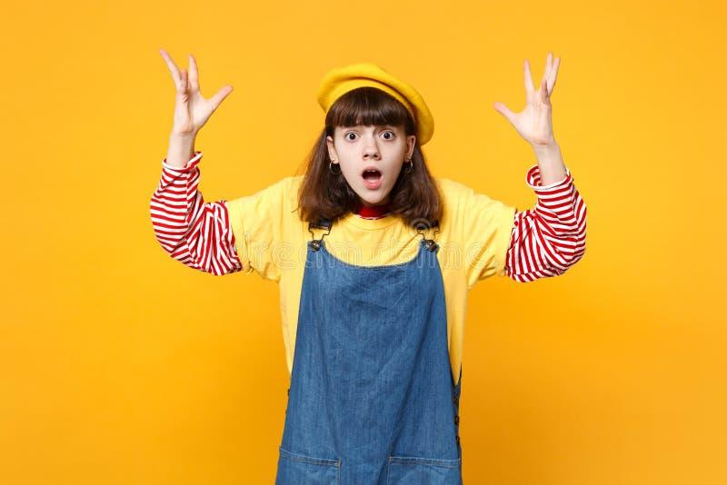 Συγκλονισμένος έφηβος κοριτσιών γαλλικό beret, τζιν sundress που διαδίδει, χέρια αύξησης που κρατούν στοματικό ευρύ ανοικτό απομο στοκ φωτογραφία με δικαίωμα ελεύθερης χρήσης