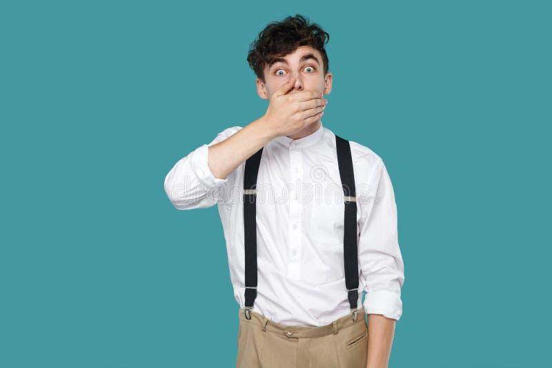 Συγκλονισμένο άτομο που καλύπτει το στόμα του, που εξετάζει τη κάμερα με τα μεγάλα μάτια στοκ εικόνα