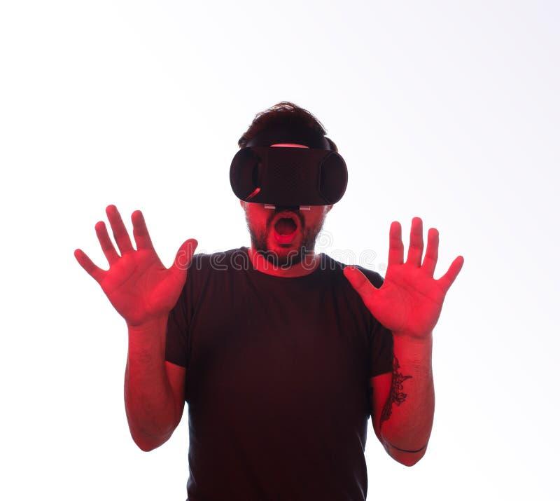Συγκλονισμένο άτομο στα προστατευτικά δίοπτρα VR με τα χέρια επάνω στοκ εικόνα