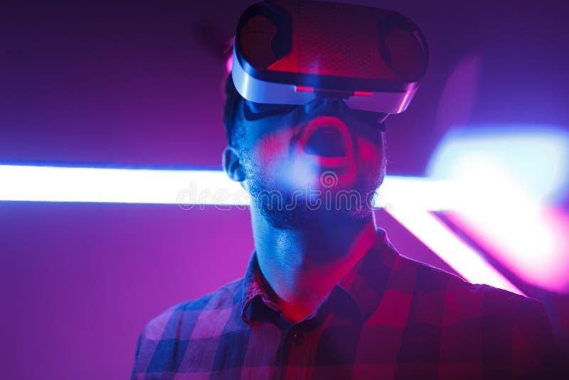 Συγκλονισμένο άτομο στα προστατευτικά δίοπτρα VR στο νυχτερινό κέντρο διασκέδασης στοκ εικόνα