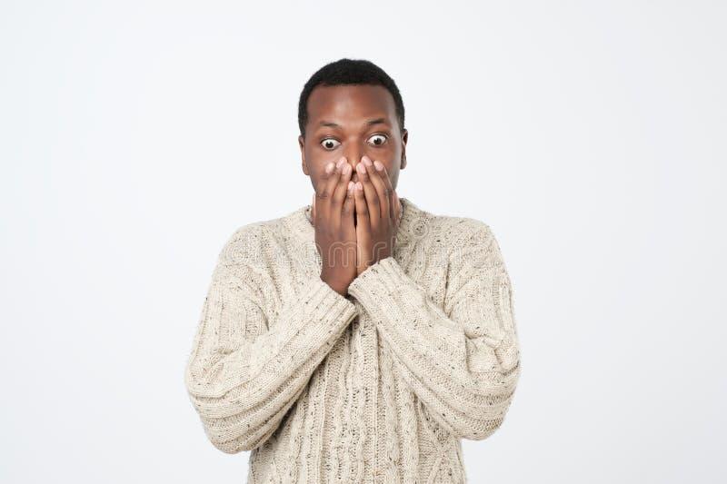 Συγκλονισμένο αφρικανικό άτομο που καλύπτει το στόμα του με τα χέρια στοκ φωτογραφία