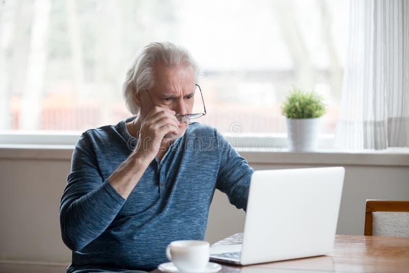 Συγκλονισμένο ματαιωμένο ανώτερο άτομο που βγάζει τα γυαλιά που εξετάζουν το lapt στοκ εικόνες