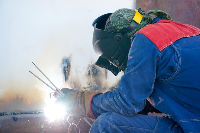 Συγκολλητής στην εργασία Χαλύβδινα φύλλα συγκόλλησης του κελύφους της δεξαμενής για πλήρωση με βενζίνη και προϊόντα πετρελαίου στ στοκ εικόνα με δικαίωμα ελεύθερης χρήσης