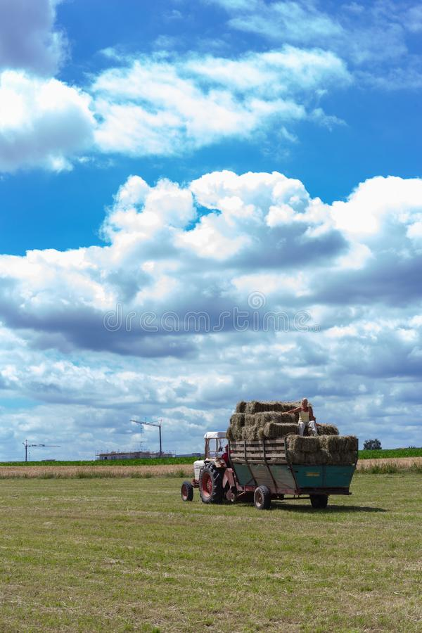 συγκομίζοντας τρακτέρ και αγρότης ρυμουλκών στοκ εικόνα με δικαίωμα ελεύθερης χρήσης