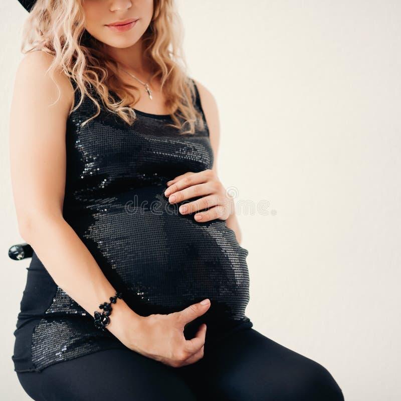 Συγκομιδή της έγκυου ξανθής γυναίκας στη μοντέρνη λαμπιρίζοντας κορυφή που αγκαλιάζει την tummy στοκ εικόνες
