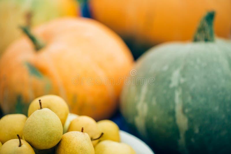 Συγκομιδή φθινοπώρου κινηματογραφήσεων σε πρώτο πλάνο, φρούτα και λαχανικά Ώριμα αχλάδια στο υπόβαθρο των μεγάλων πορτοκαλιών κολ στοκ εικόνες