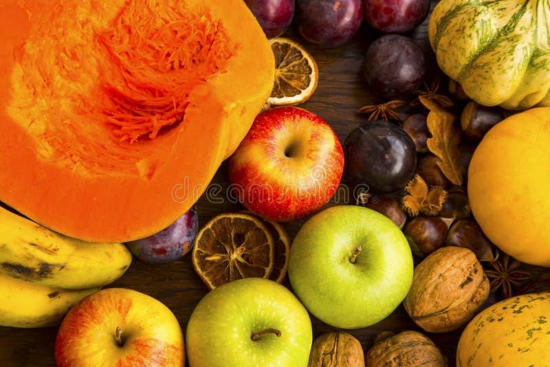 Συγκομιδή φθινοπώρου με τις κολοκύθες, την κολοκύνθη, τα δαμάσκηνα, τα μήλα και το κάστανο στοκ εικόνα