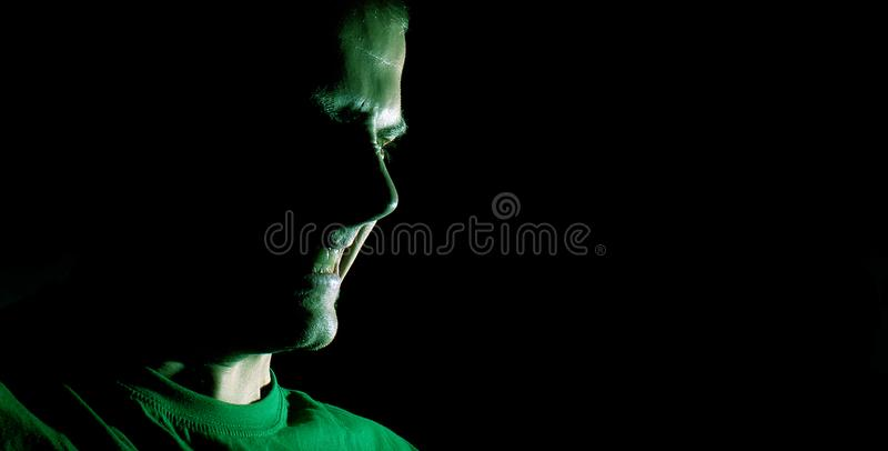 Συγκρατημένο πορτρέτο του κακού, διάβολος, κακό, πρόσωπο του ατόμου σκιαγραφία ενός ατόμου με τα σφιγγμένα δόντια σε ένα μαύρο υπ στοκ εικόνες