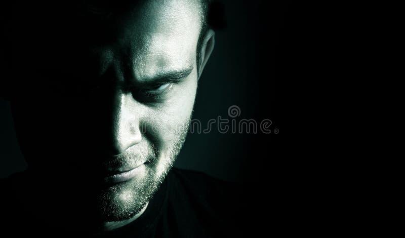 Συγκρατημένο πορτρέτο του κακού, διάβολος, κακό, πρόσωπο του ατόμου σε ένα bla στοκ εικόνες