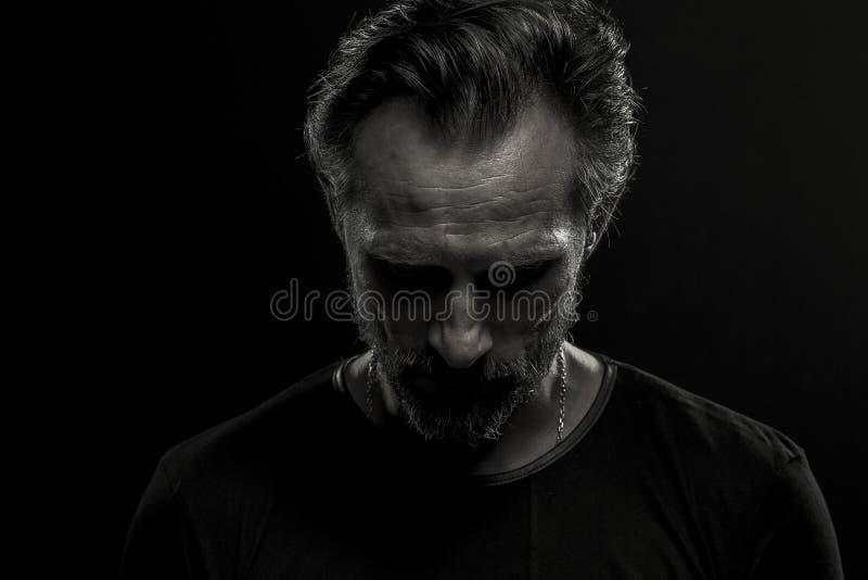 Συγκρατημένο δραματικό πορτρέτο του ώριμου ατόμου στο μαύρο υπόβαθρο στοκ εικόνες