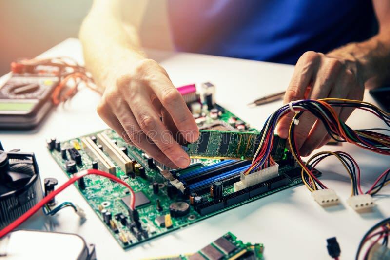 Συγκρότηση υπολογιστή - τεχνικός εγκαταστήστε τη μονάδα μνήμης ram στη μητρική πλακέτα στοκ φωτογραφία