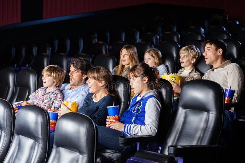 Συγκλονισμένες οικογένειες που προσέχουν τον κινηματογράφο στοκ φωτογραφίες με δικαίωμα ελεύθερης χρήσης